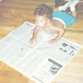 young boy reading a newspaper